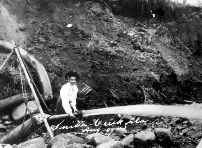 A woman demonstrates the use of a water cannon for unearthing goldrich gravels at Smith Creek just inside the Canadian border in Alaska's 40-Mile mining district, August 1907