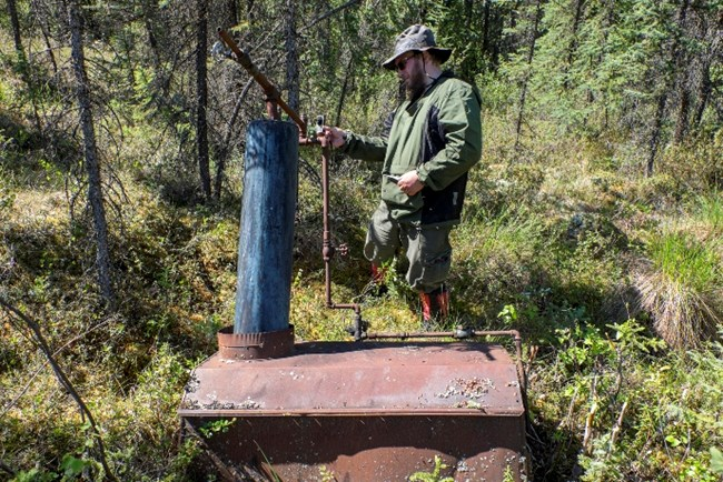 "NPS historian Chris Allan examines the ""doghouse boiler"" at Colorado Creek in Yukon-Charley Rivers National Preserve, June 2015."