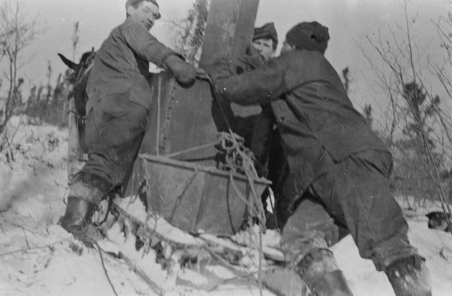 Historic photograph of men pushing a doghouse boiler uphill in winter