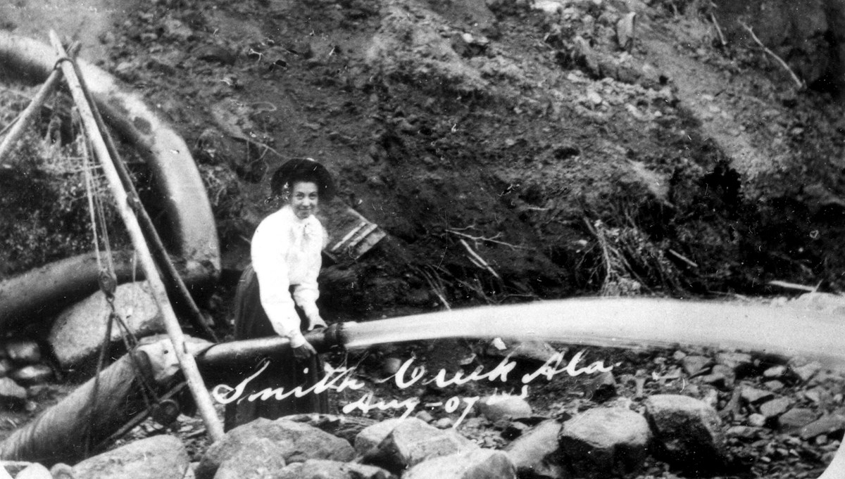 A woman demonstrates the use of a water canon for unearthing gold-rich gravels at Smith Creek just inside the Canadian border in Alaska's 40-Mile mining district, August 1907