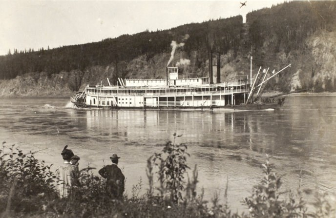 Historic photo of a riverboat on the Yukon River passing in front of the new international boundary which is a bare swath cut through the trees.