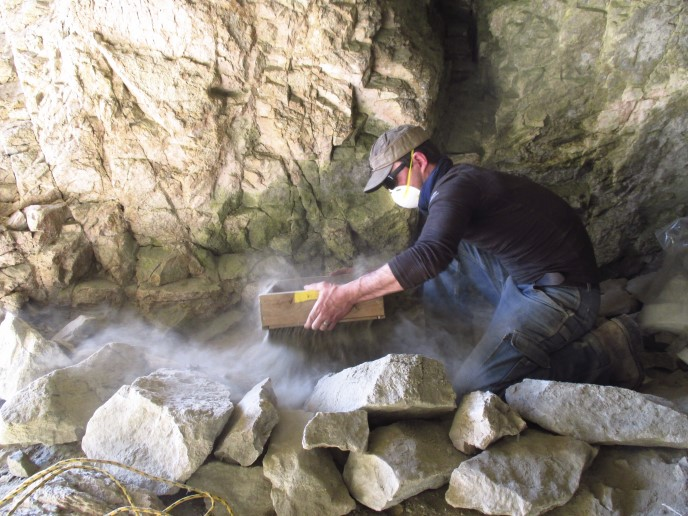 An archaeologist screens dirt in a cave.
