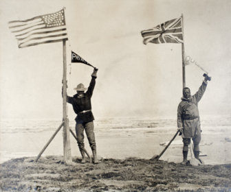Historic photo of the American and Canadian survey team leaders celebrating the end of the line at the Arctic Ocean.
