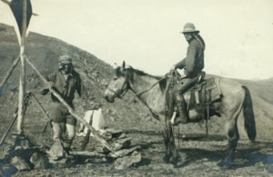 Historic photo of two surveyors, one on horseback, working on the international boundary project.