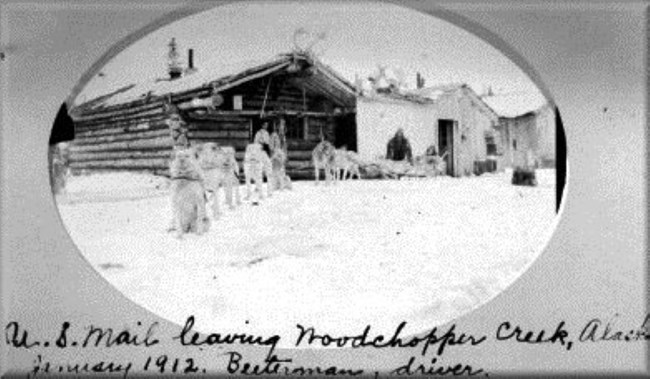 Yukon River mail carrier Ed Biederman and dog team at early Woodchopper Roadhouse buildings in 1912