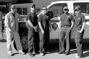 five people stand in front of a truck with a park service arrowhead logo on it