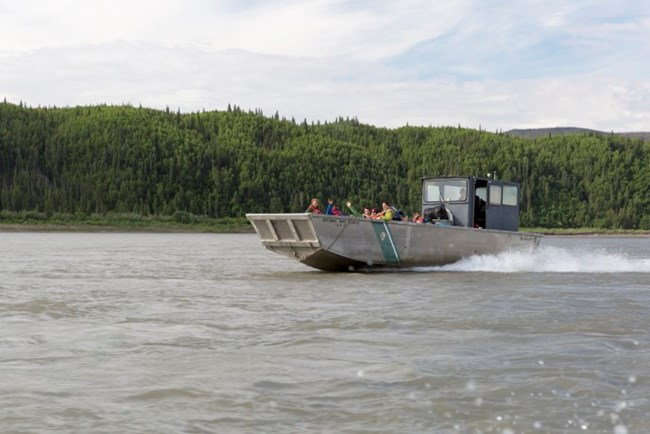 A large motorboat carries a crew of workers on the Yukon River