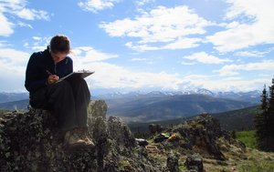 An archeologist sitting on a ridgetop drawing a site map