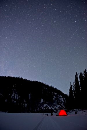 The star-filled night sky above a winter campsite on the Charley River