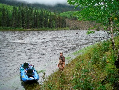 A hunter, raft, and caribou on the Charley River