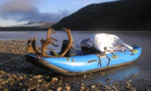 Caribou rack and game bags on a raft on a river bank