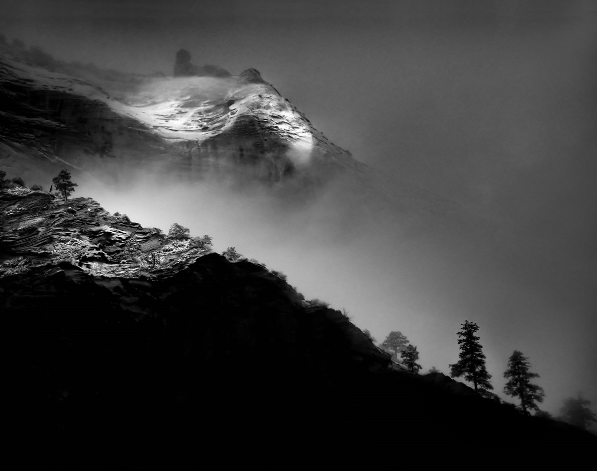 Black and white photo of snow covered canyon walls mostly obscured by fog