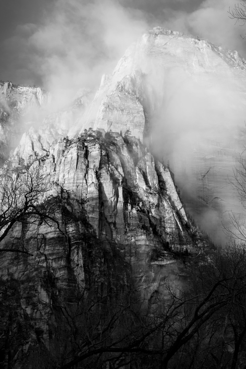 Black and white photograph of canyon walls and clouds.