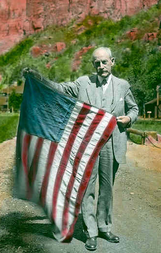 Frederick S. Dellenbaugh holding his US flag from the Powell Expedition of 1871-1872, at Zion Lodge Zion 1930, Zion Museum Collection ZION 13004-123