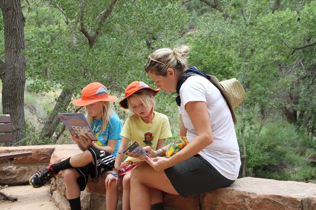 Two young park visitors working on a junior ranger book with their mother
