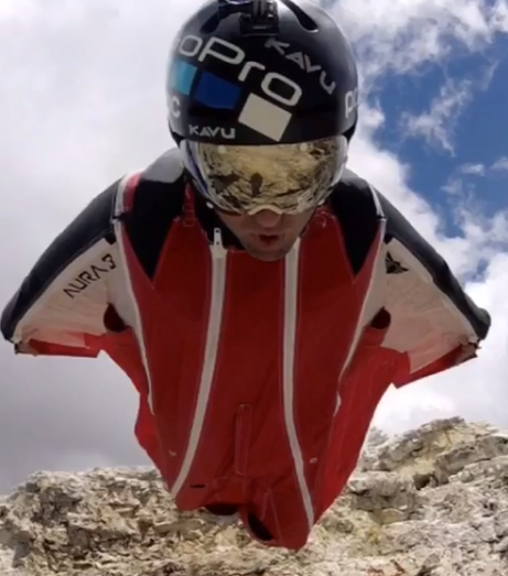 close up view from a helmet cam facing a BASE jumper in a red, white, and blue wingsuit