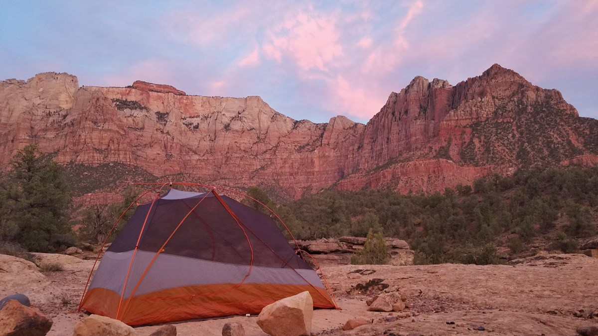 A dome tent is set up in the Zion Wilderness with massive rock walls in the background.