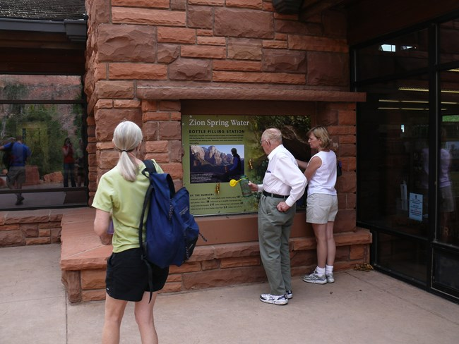 Three visitors fill their reusable water bottles at the Zion Canyon Visitor Center.