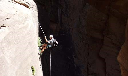 A canyoneer rappelling